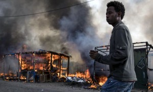 epa05603645 A migrant passes in front a fire after tents and shacks were set ablaze in the makeshift camp the 'Jungle' during its evacuation in Calais, France, 26 October 2016. The operation to dismantle the 'Jungle' migrant camp in the French port city of Calais continued into a third day. French authorities estimate that there were some 6,000 migrants living in the camp at the beginning of the week, while humanitarian organizations put the number at 8,000. Over 4,000 people have so far been bussed out of the camp to 450 reception centers across the country, according to the French Interior Ministry.  EPA/ETIENNE LAURENT